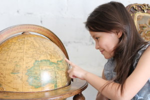 Child looking at globe earth with smiling face